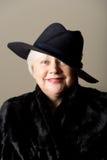 Donna dai capelli bianchi in black hat e cappotto Immagine Stock Libera da Diritti