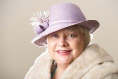 Donna dai capelli bianchi in cappello e pelliccia lilla Fotografie Stock