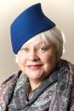 Donna dai capelli bianchi in cappello e scialle blu Immagine Stock