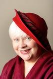 Donna dai capelli bianchi in cappello e scialle rossi Immagine Stock