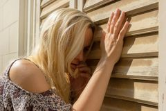 Donna dai capelli bionda che si appoggia i ciechi di finestra, sguardo triste fotografia stock