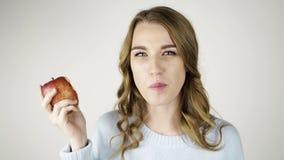 Donna dai capelli giusta che morde una mela rossa e che flirta stock footage