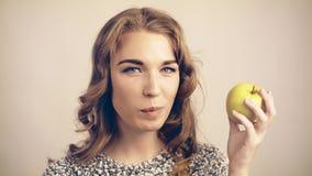 Donna dai capelli leggera che morde una mela verde e che esamina macchina fotografica tonificata video d archivio