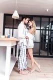 Donna dai capelli lunghi bionda di stupore in vestiti domestici piacevoli che abbracciano il suo marito fotografie stock