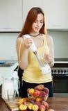 Donna dai capelli lunghi che cucina le bevande dalle pesche Immagine Stock Libera da Diritti