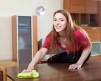 Donna dai capelli lunghi che pulisce tavola di legno con lo straccio Immagine Stock