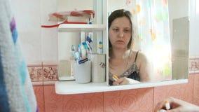 Donna dai capelli lunghi di peso eccessivo che pulisce i suoi denti nel bagno la ragazza in camicia da notte blu ha riflesso in u stock footage