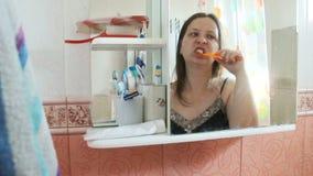 Donna dai capelli lunghi di peso eccessivo che pulisce i suoi denti nel bagno la ragazza in camicia da notte blu ha riflesso in u archivi video