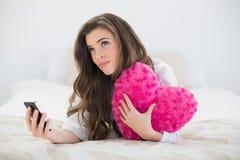 Donna dai capelli marrone casuale pensierosa in pigiami bianchi che tengono un telefono cellulare e un cuscino in forma di cuore Fotografia Stock