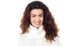 Donna dai capelli riccia che posa contro il bianco Immagine Stock