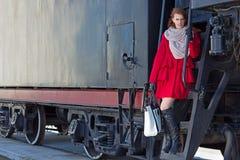 Donna dai capelli rossi in cappotto rosso e treno d'annata immagine stock