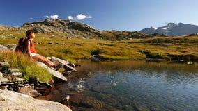 Donna dai capelli rossi con lo zaino che prende un sunbath di rilassamento che si siede alla banca del lago dell'alta montagna Vi video d archivio