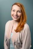 Donna dai capelli rossi sorridente che esamina macchina fotografica Immagine Stock