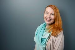 Donna dai capelli rossi sorridente con la sciarpa che esamina macchina fotografica Fotografia Stock