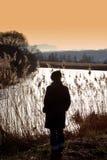 Donna dal lago in campagna Fotografia Stock