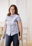 Donna danneggiata che per mezzo delle grucce per camminare Immagini Stock Libere da Diritti