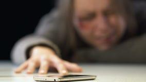 Donna danneggiata che prova a prendere telefono per chiamare 911, vittima dell'incidente o disastro stock footage