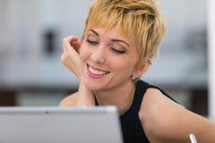 Donna in datazione di oline su un punto di Internet pubblico fotografie stock libere da diritti