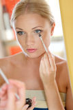Donna davanti allo specchio che mette trucco Immagini Stock