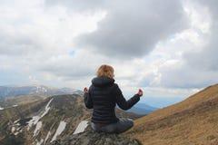 Donna dei capelli biondi che ha una meditazione sul picco di montagna Fotografia Stock