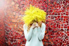 Donna dei pantaloni a vita bassa con un mazzo della mimosa immagine stock libera da diritti