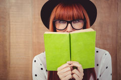 Donna dei pantaloni a vita bassa dietro un Libro verde Immagine Stock