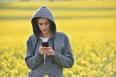 Donna dei pantaloni a vita bassa in maglia con cappuccio facendo uso del suo Smart Phone dentro all'aperto Fotografia Stock