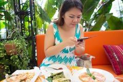 Donna del Asean che fotografa alimento Immagini Stock Libere da Diritti