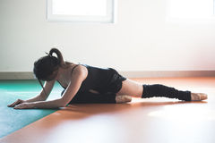 Donna del ballerino che fa allungamento sulla classe di balletto Fotografia Stock