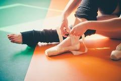 Donna del ballerino che mette sulle scarpe di balletto Fotografie Stock Libere da Diritti