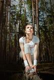 Donna del corridore che allunga coscia prima dell'correre nella foresta e dello sguardo al cielo Fotografie Stock