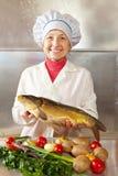 Donna del cuoco con la carpa Fotografia Stock