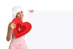 Donna del cuoco unico che mostra tabellone per le affissioni con forma del cuore Fotografia Stock