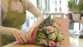 Donna del fiorista con i fiori e l'uomo al negozio di fiore video d archivio