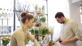 Donna del fiorista con i fiori e l'uomo al negozio di fiore stock footage