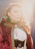 Donna del guerriero con la spada in vestiti medievali alla luce del sole Fotografie Stock Libere da Diritti