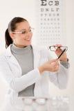Donna del medico dell'ottico con i vetri ed il diagramma di occhio immagine stock