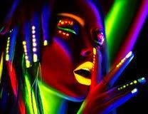 Donna del modello di moda alla luce al neon Bella ragazza di modello con trucco fluorescente variopinto fotografie stock