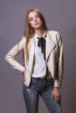 Donna del modello di moda in cappotto e jeans del cuoio bianco immagini stock libere da diritti