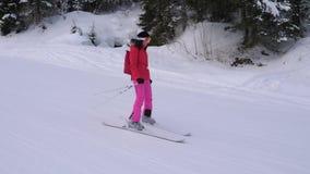 Donna del movimento che scia giù Ski Slope In The Mountain fra l'abetaia stock footage