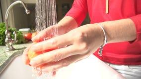 Donna del movimento lento che lava una verdura video d archivio