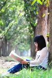 Donna del nerd che legge il taccuino di cuore rosso Fotografie Stock Libere da Diritti