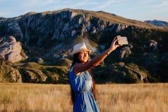 Donna del paese che fa la foto del selfie in montagne Immagini Stock Libere da Diritti
