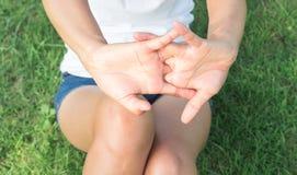 Donna del primo piano che allunga il dito di esercizi nel parco con il sole l Fotografie Stock