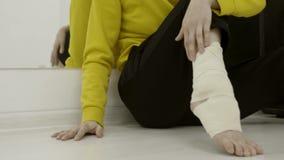 Donna del primo piano che benda la sua gamba con la fasciatura elastica azione Lesione o allungamento inattesa della caviglia men archivi video