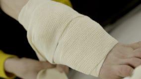 Donna del primo piano che benda la sua gamba con la fasciatura elastica azione Lesione o allungamento inattesa della caviglia men video d archivio