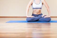 Donna del primo piano che fa esercizio di yoga dell'interno Fotografia Stock Libera da Diritti