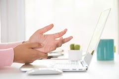 Donna del primo piano che tiene il suo dolore del polso dal per mezzo del computer ufficio immagine stock