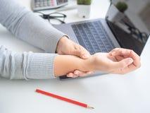 Donna del primo piano che tiene il suo dolore del polso dal usando il Ti del computer lungamente immagine stock