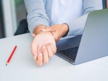 Donna del primo piano che tiene il suo dolore del polso dal usando il Ti del computer lungamente fotografie stock libere da diritti